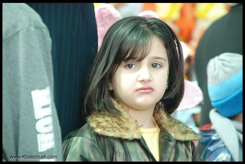 طفلة جميلة مهندمة الثياب ومنسقة الشعر تنظر بثقة واتزان للعدسة