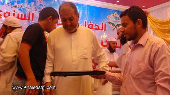 الطالب الحافظ إبراهيم البنا (يسار) يستلم جائزة تشجيعية من والده لاكماله حفظ القرآن الكريم وهي جهاز كمبيوتر محمول